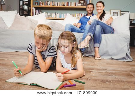 Children coloring on book while parents looking at them from sofa in living room