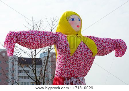 Scarecrow of Shrovetide in bright multi-colored costume on background of sky and city building