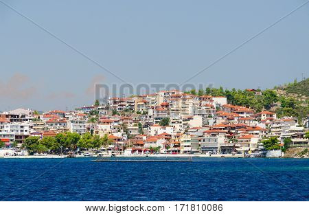 View from sea on promenade in popular small resort town of Neos Marmaras Sithonia Peninsula Greece