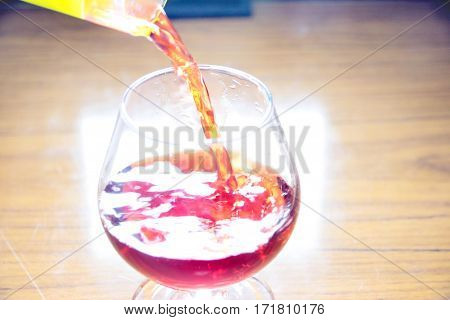 lovely red wine is poured into a glass for human consumption