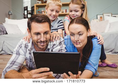 Parents holding digital tablet lying on floor while kids sitting on their back at home