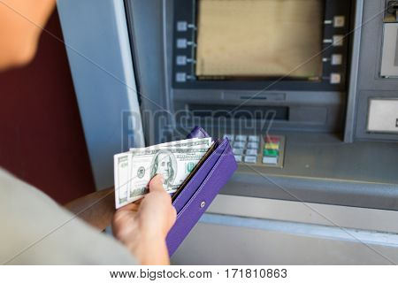 finance, money, bank and people concept - close up of hand with wallet withdrawing cash at atm machine