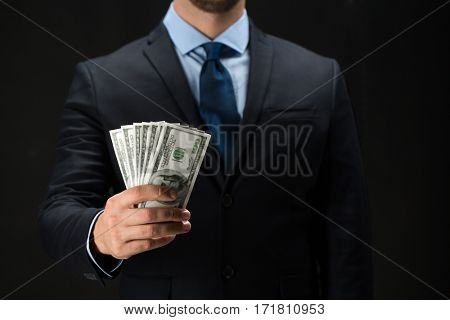 people, business, finances and money concept - close up of businessman hands holding dollar cash over black background