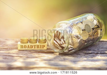 Roadtrip Word Golden Coin Stacked With Wooden Bar On Shallow Dof Green Background.