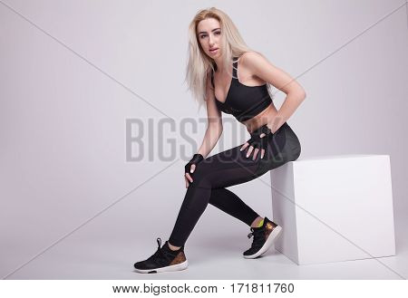 Caucasian female athlete sitting on a box. Fit young woman taking break after her workout at gym.