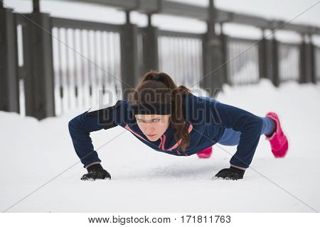 Fitness girl doing pushups on work out fitness at snow winter park, telephoto