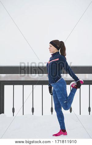 Female runner doing flexibility exercise for legs before run at snow winter promenade, vertical, telephoto
