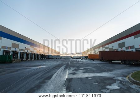 logistic, storage, shipment, transportation and loading concept - warehouse gates and trucks loading