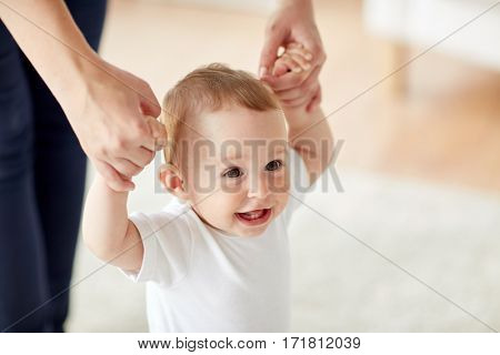 family, child, childhood and parenthood concept - close up of happy little baby learning to walk with mother help at home