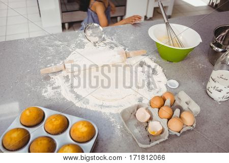 High angle view of rolling pin on dough with muffins and egg at kitchen table