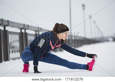 Woman runner stretching legs before run. Young athlete woman working out. Fitness concept, telephoto