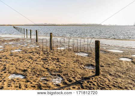 Fence of wooden poles and barbed wire diagonal in the image of a flooded area in the Dutch winter season.
