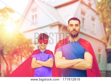 family, power and people concept - man and boy wearing mask and red superhero cape over house background