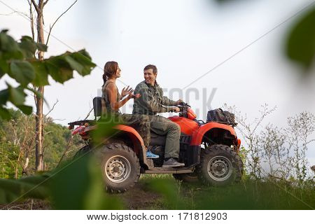 Man And Woman Are Discussing Their Trip While Sitting On A Quadbike.