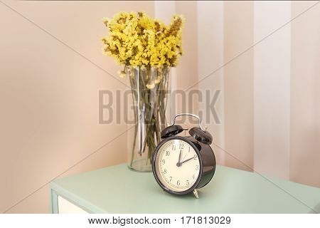Nightstand with flower vase and Alarm clock