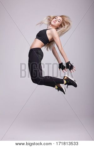 Beautiful young blonde fit woman with long hair happily jumping on a grey background. Slim woman in sport clothes.