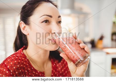 Close-up of woman drinking fruit juice while standing at home