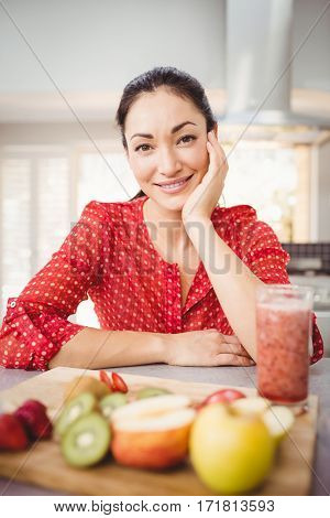 Portrait of happy woman with fruit juice on table at home