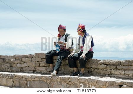 Two men dressed in traditional outfits specific for the Taquile Island region one of them knitting a hat. Lake Titicaca Peru - October 17 2012