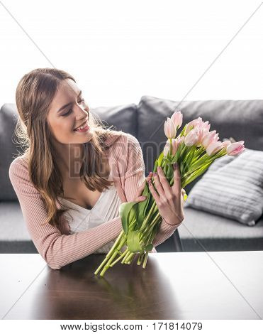 Young smiling woman holding bouquet of fresh tulip flowers