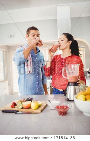 Smiling couple drinking fruit juice while standing at home