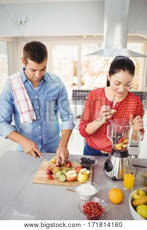 Couple preparing fruit juice while standing at table
