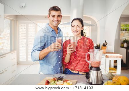 Portrait of smiling couple holding fruit juice while standing at home