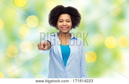 people, race, ethnicity, gesture and choice concept - happy african american young woman pointing finger to you over summer green lights background