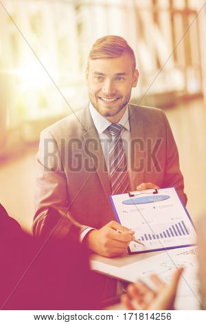 business, people and statistics concept - happy smiling young businessman with graph on clipboard meeting with colleague at office