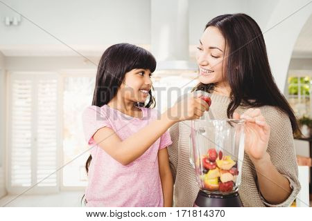 Mother and daughter preparing fruit juice at home
