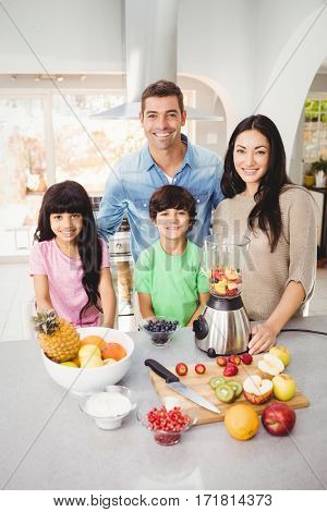 Portrait of smiling family preparing fruit juice at table