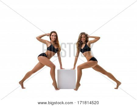 Pretty girls in black tops and shorts posing together by the cube studio shot