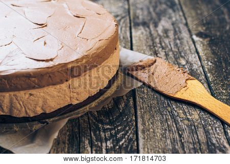 Delicious chocolate mousse cake on the old wooden backround. Selective focus.