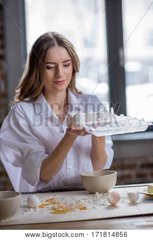 Smiling young woman holding egg box while cooking healthy breakfast