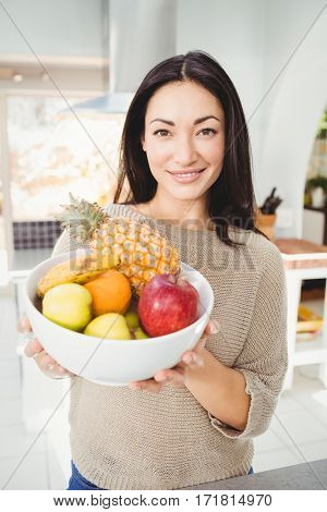 Portrait of smiling woman holding fruits bowl while standing at home