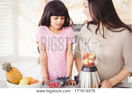 Happy mother and daughter preparing fruit juice at home