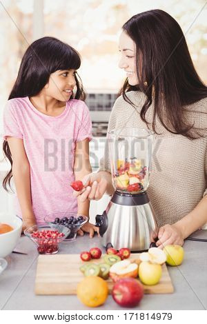 Cheerful mother and daughter preparing fruit juice at home