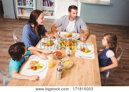 Family discussing with food on dining table at home
