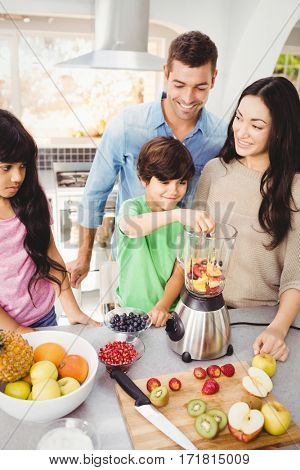 Cheerful family preparing fruit juice at home