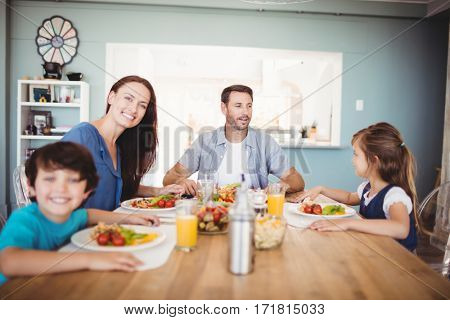 Smiling family with food on dining table at home