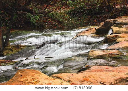 White water of the fast flowing Travertine creek at the Chickasaw National Recreation Park in Davis, Oklahoma, cascading over rocks with autumn colored leaves and trees in the background.