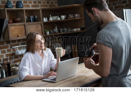 Smiling young couple drinking coffee while using laptop