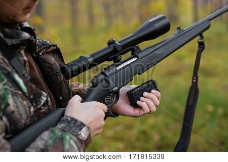 Hunter loading rifle for shooting in the woods