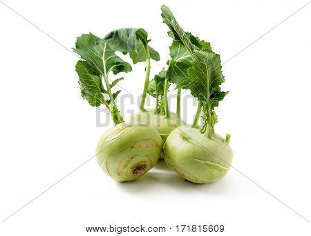Three fresh kohlrabi with green leaves.
