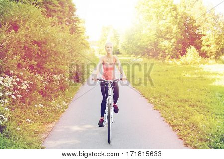 fitness, sport, people and healthy lifestyle concept - happy young woman riding bicycle outdoors