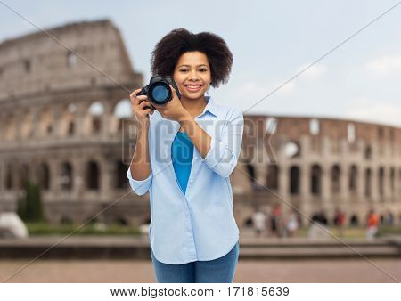 travel, tourism, people and photography concept - happy african american young woman with digital camera over coliseum background