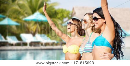 summer holidays, travel, people and vacation concept - happy young women in bikinis and shades hugging and waving hands over swimming pool background