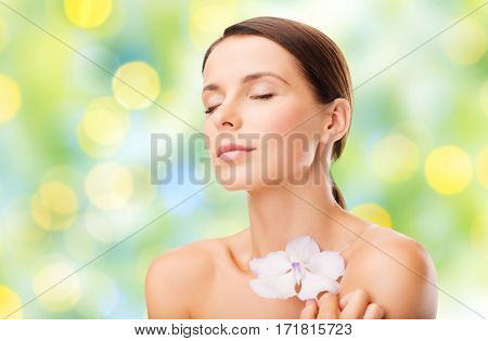 beauty, people, bodycare and health concept - beautiful young woman with orchid flower and bare shoulders over summer green lights background