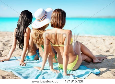 summer holidays, vacation, travel and people concept - group of women in swimwear sunbathing over exotic tropical beach background