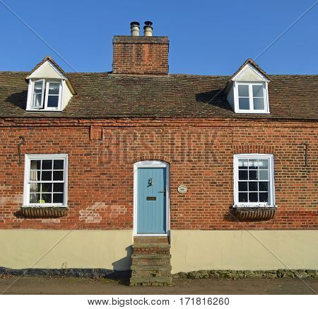 GAMLINGAY, CAMBRIDGESHIRE, ENGLAND - FEBRUARY 14, 2017: Old Cottage with steps to a very high front door.